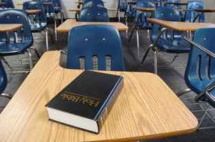 a classroom full of desks and chairs with a holy bible on one desk