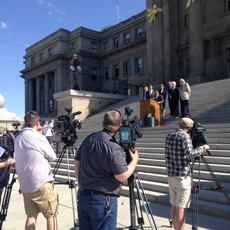 Press conference in front of the Idaho Statehouse. cameras in the fore ground, people beyond a podium in the background