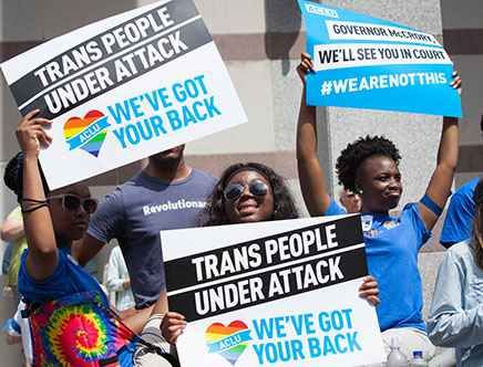 """A group of young black people hold up signs in the sunshine that say """"trans people are under attack, we've got your back"""""""