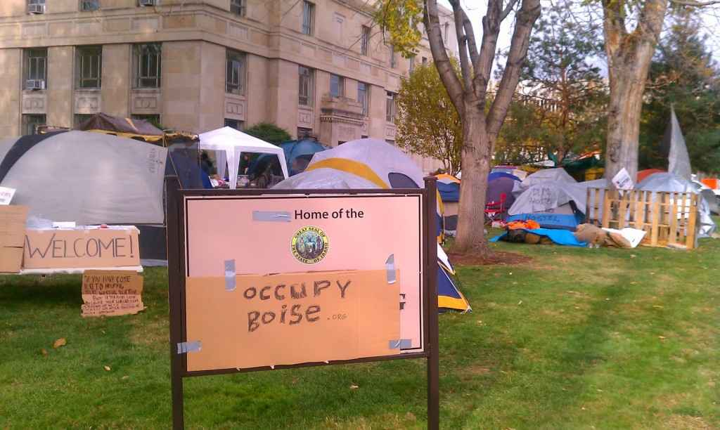 "Occupy Boise tents and signs on the lawn of the old Ada County Courthouse, with a cardboard sign in front reading ""Occupy Boise"""