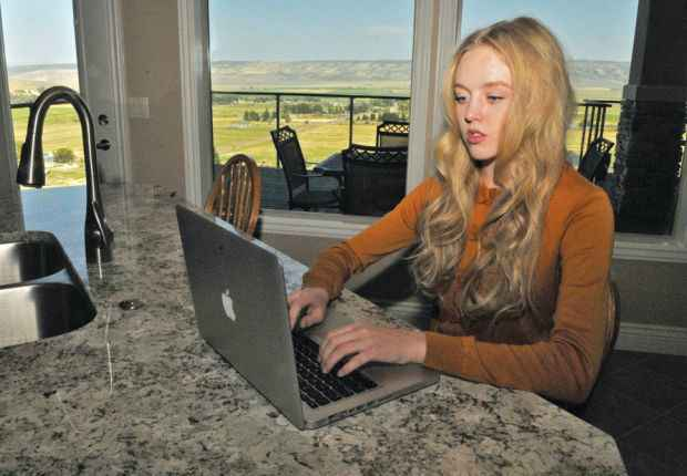 Woman sitting at a countertop looking at a laptop in a room with windows looking out to what looks like farmland